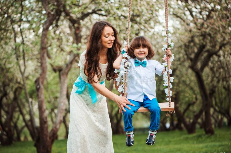 Happy dressy mother and toddler child son having fun on swing in spring or summer park, wearing bow tie and long lacy dress for bi royalty free stock photo
