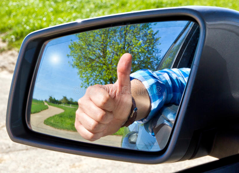 Happy driver. With thumb up in side-view mirror stock photography
