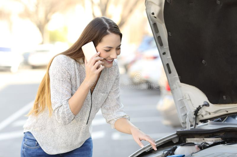 Happy driver with car breakdown calling insurance. On the street stock photography