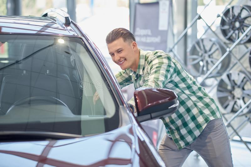 Happy driver choosing new vehicle in auto salon in smiling. Young attractive man leaning on front of red car. Handsome blond client in jeans and checkered shirt royalty free stock images
