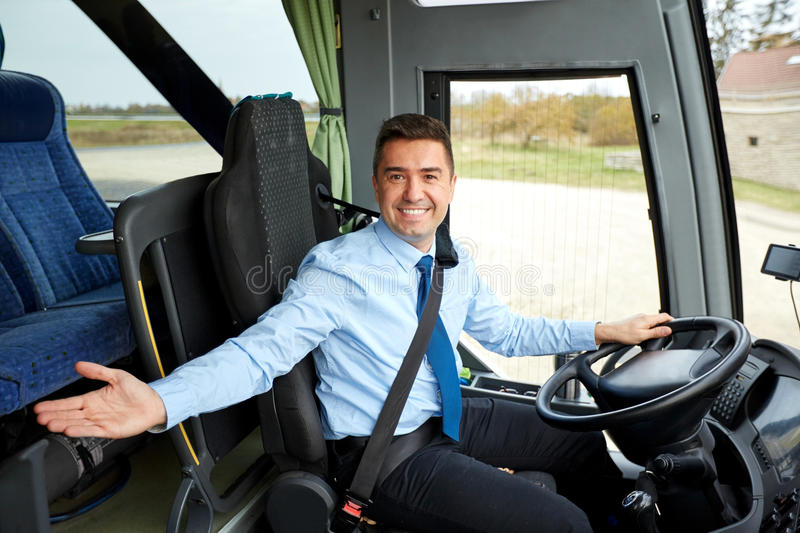 Happy driver inviting on board of intercity bus. Transport, tourism, road trip, gesture and people concept - happy driver inviting on board of intercity bus royalty free stock photography