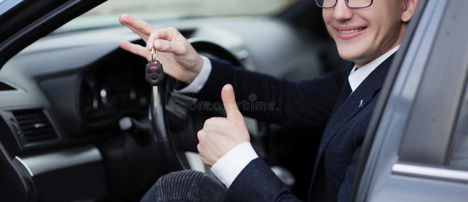 Happy driver showing thumb up while sitting in his car royalty free stock images