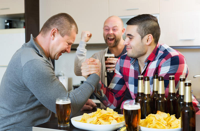 Happy and drunk men armwrestling. Their friend supporting royalty free stock image