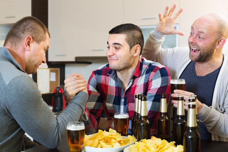 Happy and drunk men armwrestling. Their friend supporting in kitchen stock photo
