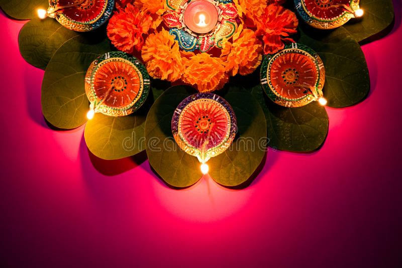 Happy Dussehra. Clay Diya lamps lit during Dussehra with yellow flowers, green leaf and rice on pink pastel background. Dussehra. Indian Festival concept stock photography