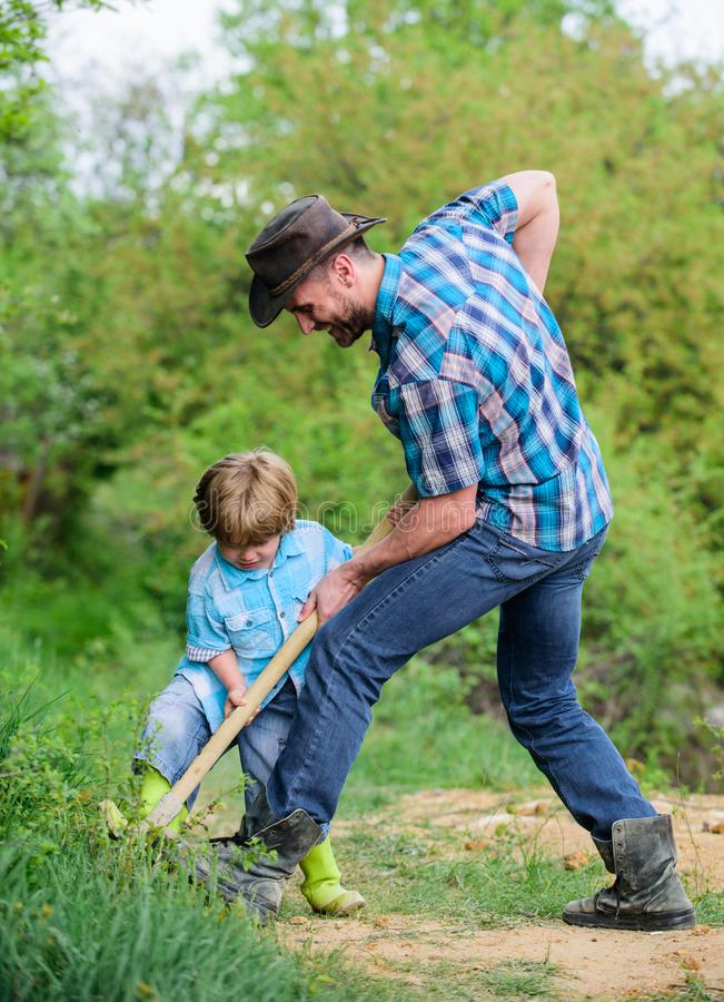 Happy earth day. Dig grounf with shovel. new life. soils and fertilizers. rich natural soil. Eco farm. Ranch. small boy. Child help father in farming. father stock images