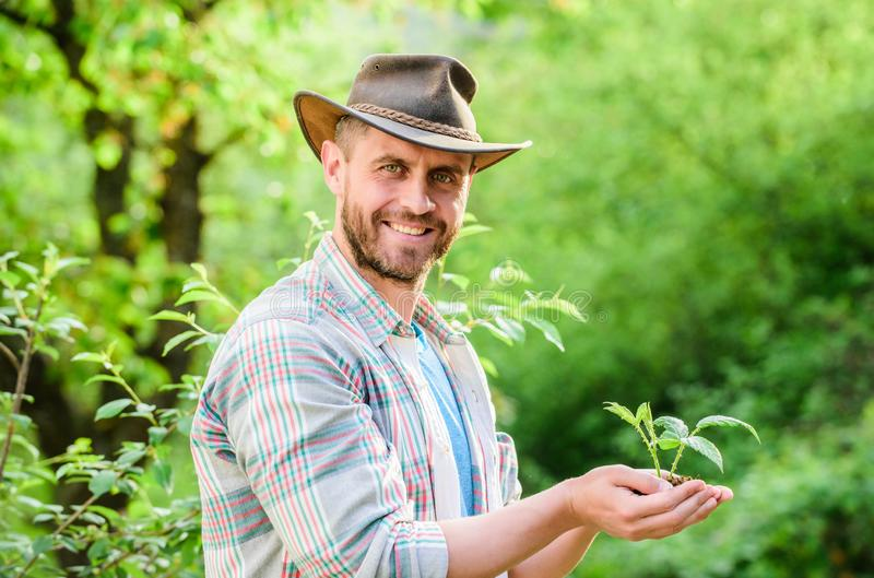 Happy earth day. Eco living. farming and agriculture cultivation. Gardening. muscular ranch man in cowboy hat care. Plants. successful farmer hold plant in stock image