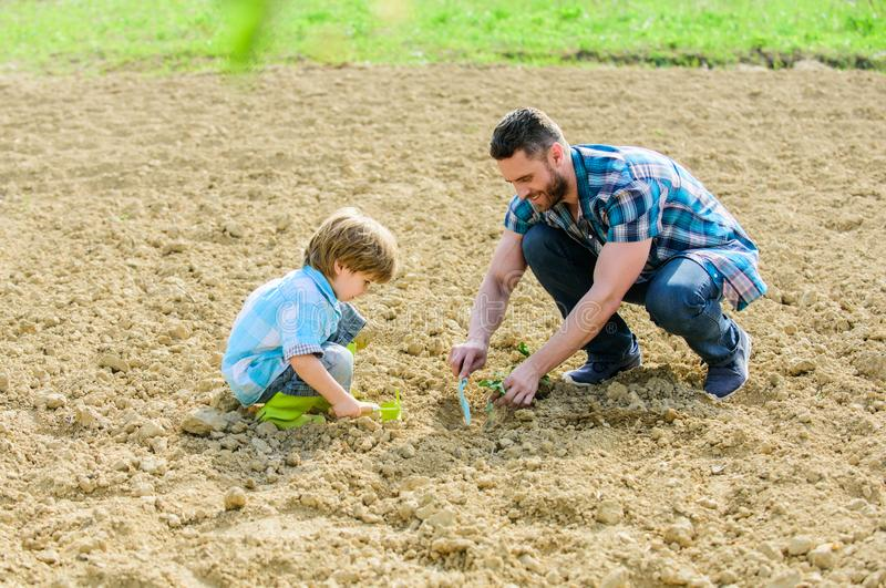 Happy earth day. Family tree. father and son planting flowers in ground. small boy child help father in farming. earth. Day. new life. soils fertilizers. rich stock images