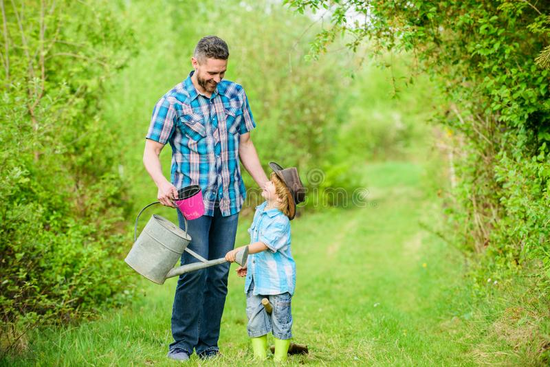 Happy earth day. Family tree nursering. Eco farm. small boy child help father in farming. use watering can and pot royalty free stock photo