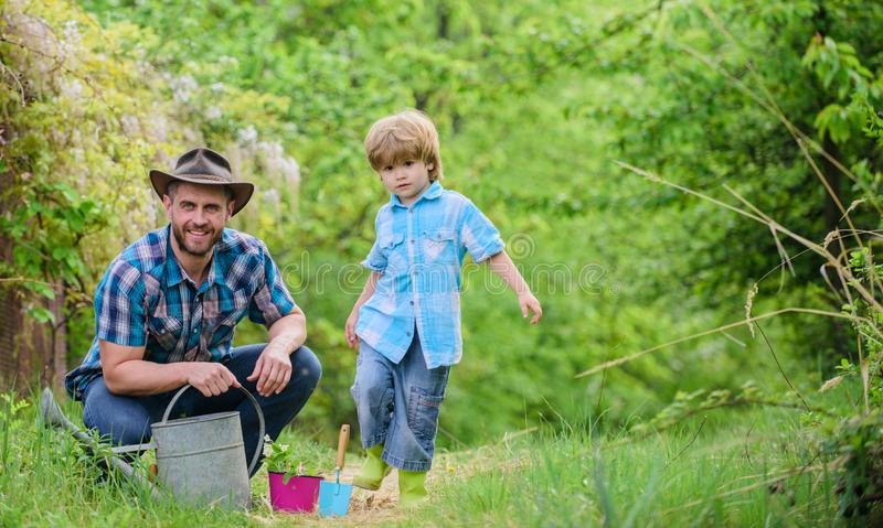 Happy earth day. Family tree nursering. Eco farm. small boy child help father in farming. watering can, pot and hoe stock images