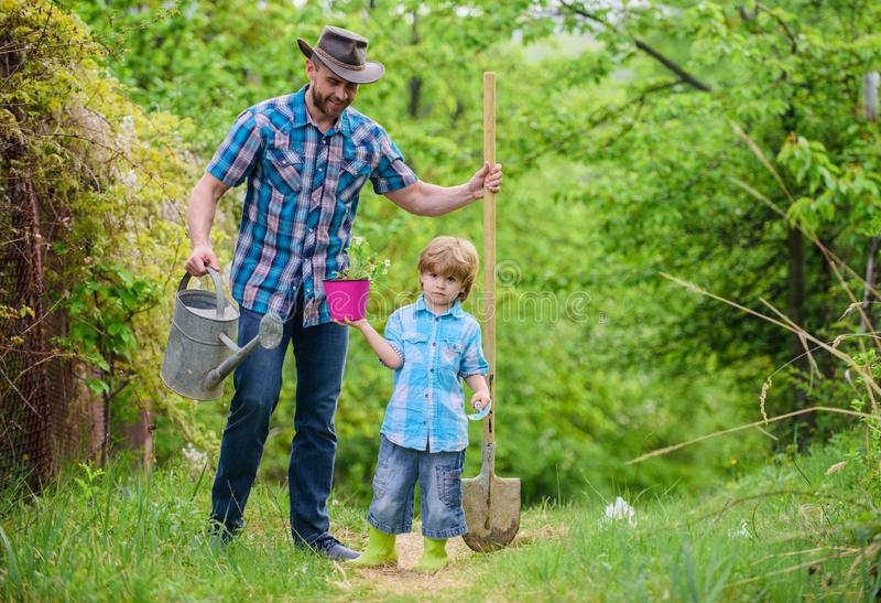 Happy earth day. Family tree nursering. Eco farm. small boy child help father in farming. watering can, pot and shovel. Garden equipment. father and son in royalty free stock image