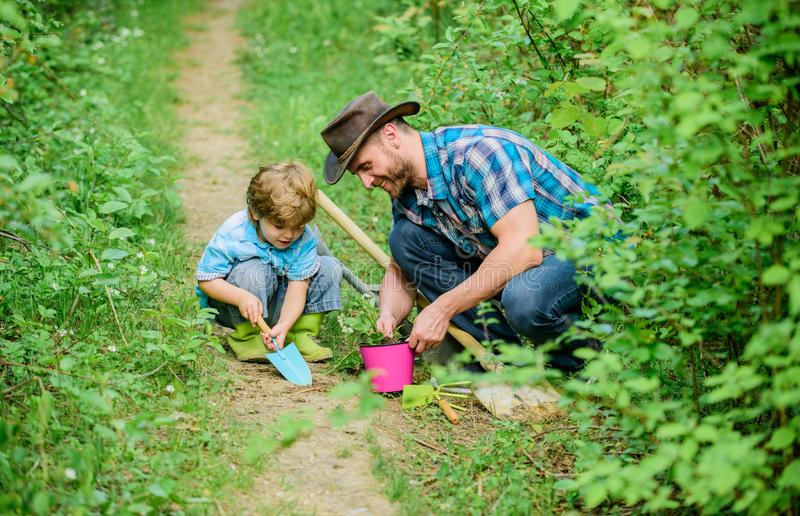Happy earth day. Family tree nursering. father and son in cowboy hat on ranch. hoe, pot and shovel. Garden equipment. Eco farm. small boy child help father in royalty free stock photography
