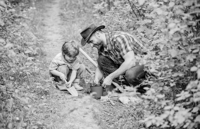 Happy earth day. Family tree nursering. father and son in cowboy hat on ranch. hoe, pot and shovel. Garden equipment. Eco farm. small boy child help father in stock photo