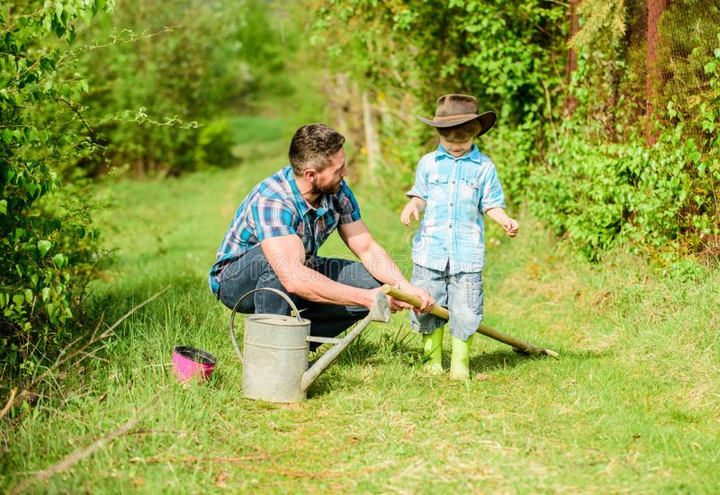Happy earth day. Family tree nursering. father and son in cowboy hat on ranch. use watering can and pot. Garden. Equipment. Eco farm. small boy child help royalty free stock images