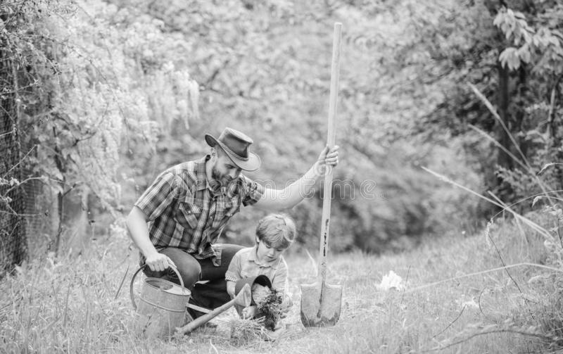 Happy earth day. Family tree nursering. watering can, pot and shovel. Garden equipment. Eco farm. small boy child help. Father in farming. father and son in stock photo