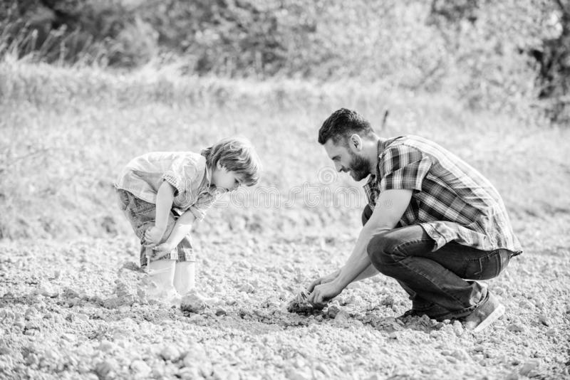 Happy earth day. Family tree. rich natural soil. Eco farm. small boy child help father in farming. new life. Ecological. Engineering. father and son planting royalty free stock photo