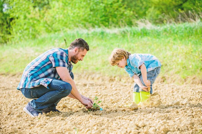 Happy earth day. Family tree. rich natural soil. Eco farm. small boy child help father in farming. new life. Ecological. Engineering. father and son planting stock photos