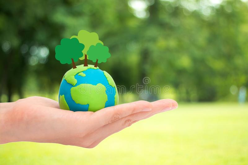 Happy earth day. Human hands holding plant trees on the globe, planet or earth over blurred green garden nature background. Ecology concept royalty free stock photo