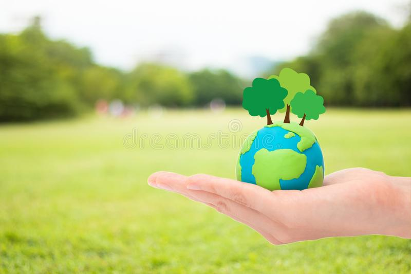 Happy earth day. Human hands holding plant trees on the globe, planet or earth over blurred green garden nature background. Ecology concept stock photo
