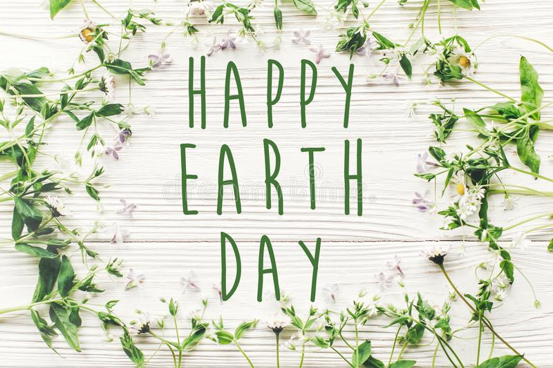 Happy earth day text sign on beautiful lilac and daisy flowers o. N rustic white wooden background top view. greeting card. environmental concept. earth day stock photography