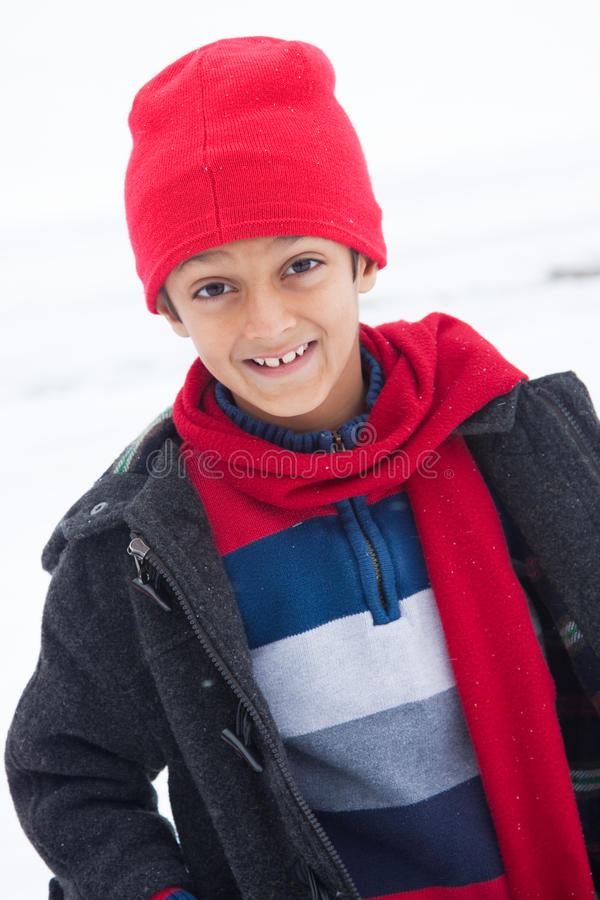 Happy East Indian boy playing in the snow stock photos