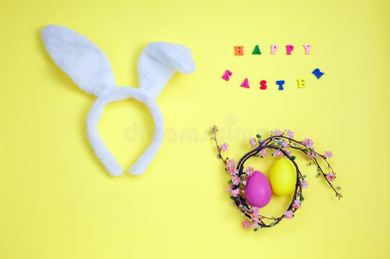 Happy easter with adorable bunny ears on a bird nest with colorful eggs against on yellow background royalty free stock images