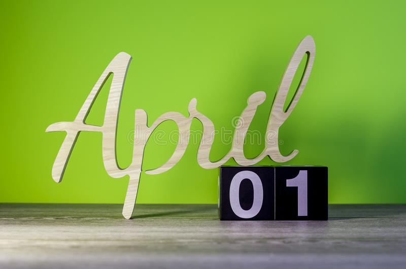 Happy Easter. April 1st. Day 1 of month, calendar on wooden table and green background. Spring time.  stock photography