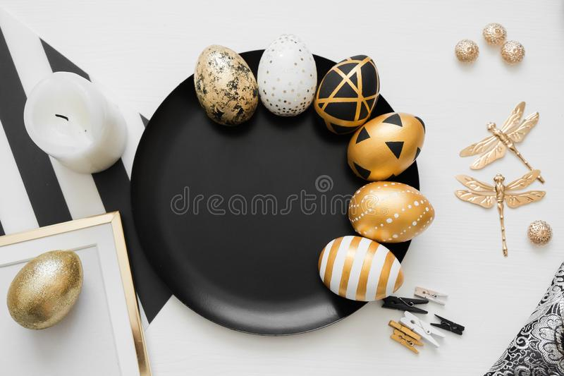 Happy Easter background with golden decorated eggs on black plate isolated on white background. Trendy flat lay easter. stock images