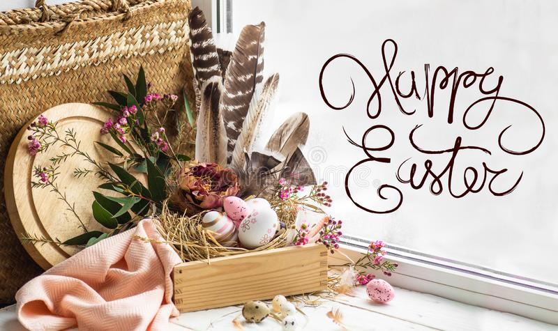 Happy Easter background. Pink Easter eggs in a nest with floral decorations and feathers near the window stock images