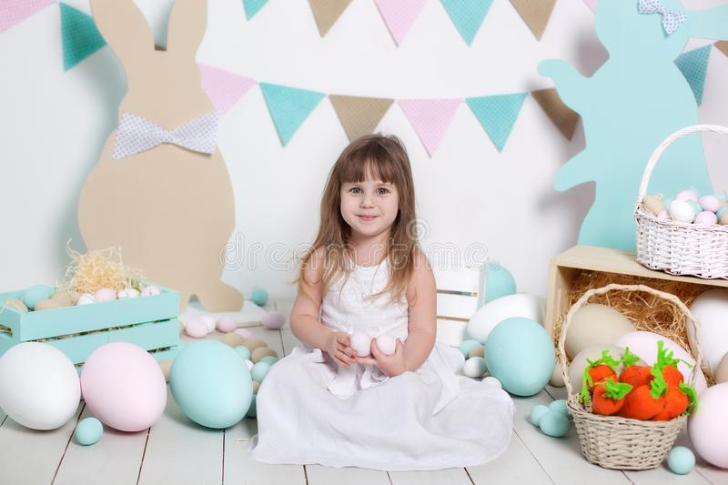 Happy Easter!A beautiful little girl in a white dress sits near a bright scenery and holds an Easter egg. Easter bunny and carrot. royalty free stock images