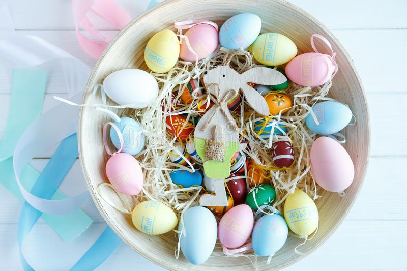 Happy Easter! Bowl with hand painted colorful eggs on white wooden table. Close up. Decoration for Easter stock photos