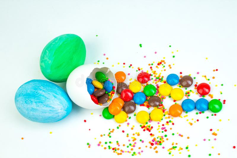 Happy Easter. Broken Easter egg with multi-colored candy decorations. on white background. Copy space for text stock photography