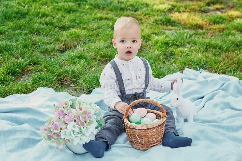 Happy Easter bunny. Child having fun outdoor. Kid playing with eggs and rabbit on green grass. Spring holidays concept. Easter stock images