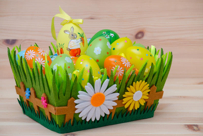 Happy easter bunny with eggs in a basket and. Easter bunny with easter eggs in a basket on the wooden background royalty free stock image