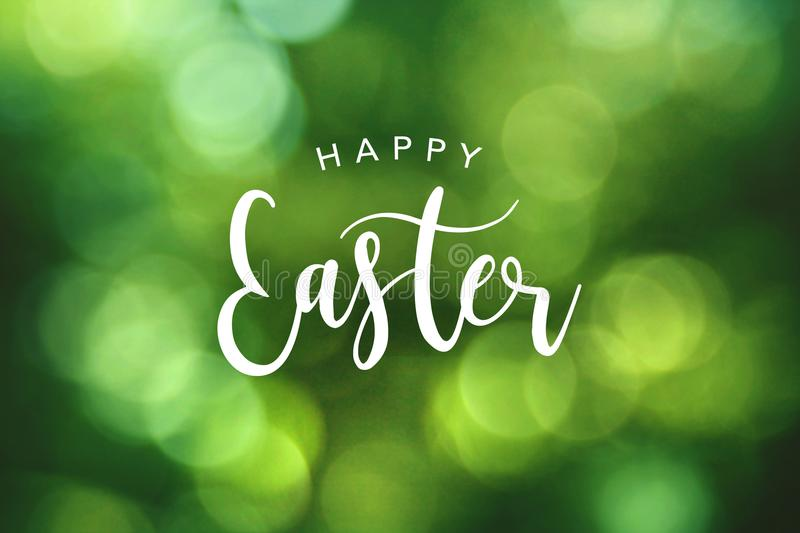 Happy Easter Calligraphy Text Over Green Spring Bokeh Background royalty free stock photography