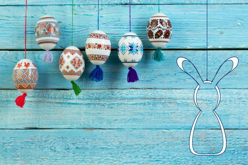 Happy Easter card. Colorful shiny easter eggs and rabbit on blue wooden table background. Copy space for text. stock photo