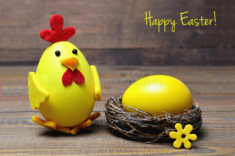 Happy Easter card: Easter chick and egg in the nest. On wooden background stock images
