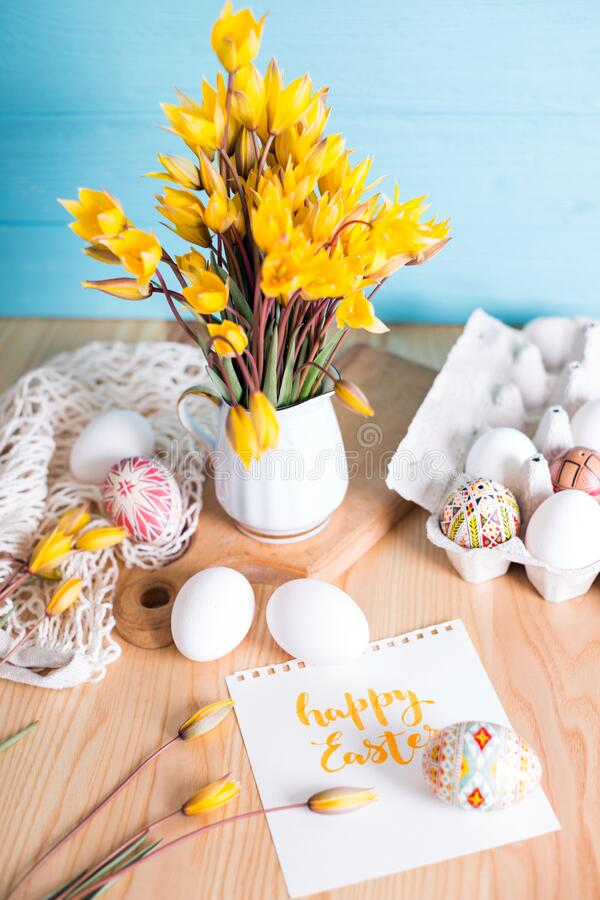 Happy easter card. Still life - beautiful Easter egg Pysanka handmade and bouquet of wild tulips with inscription happy easter stock image