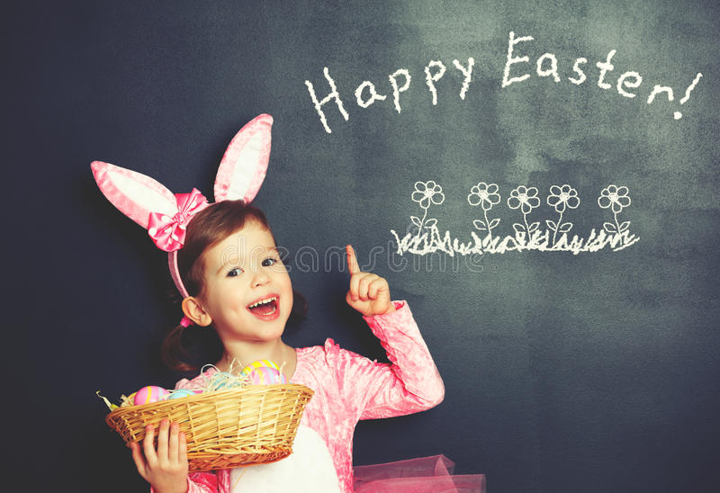 Happy Easter! child girl in costume bunny rabbit with basket of. Happy Easter! child girl in costume bunny rabbit with ears and basket of eggs about blackboard royalty free stock photo