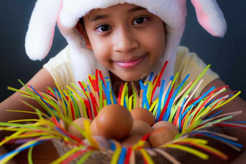 Happy easter! Close up cute girl wearing rabbit hat with chicken eggs in a basket royalty free stock image