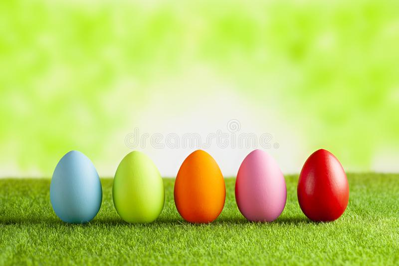 Happy Easter - Colored eggs on grass and green abstract background stock images