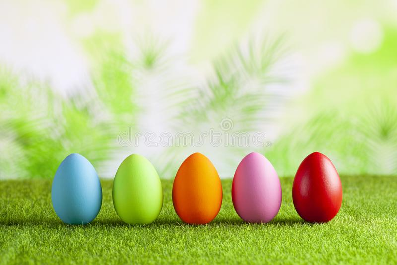 Happy Easter - Colored eggs on grass and green abstract background royalty free stock images
