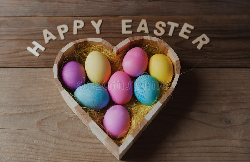 Happy Easter - colored eggs in a heart shaped bowl stock photography