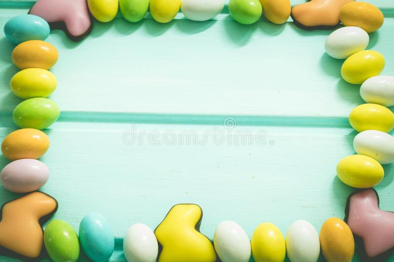 Happy Easter. Colorful candy eggs and chocolate rabbits on blue background. Frame. Top view. Copyspace. Happy Easter. Colorful candy sweet eggs and chocolate stock photo