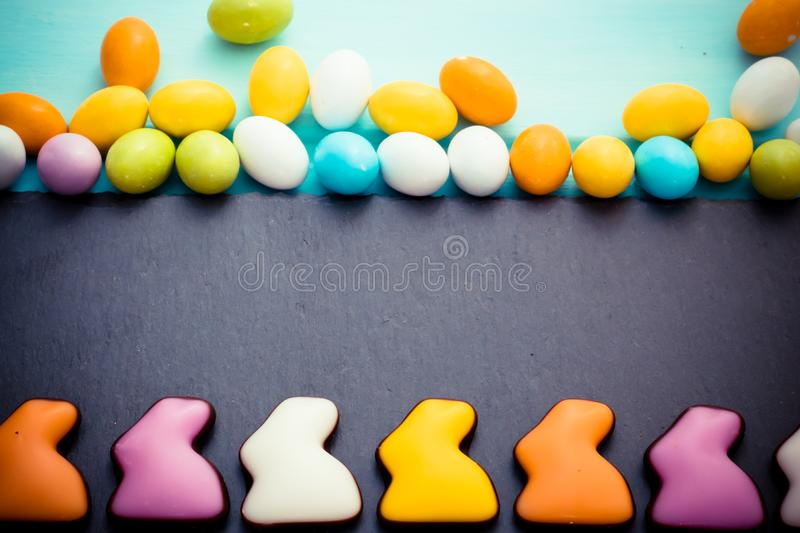 Happy Easter. Colorful chocolate rabbits in a row with small eggs on slate board. Top view. Copyspace. Happy Easter. Colorful chocolate rabbits in a row with stock photos