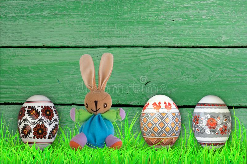 Happy Easter. Colorful easter eggs and rabbit on green grass. royalty free stock photo
