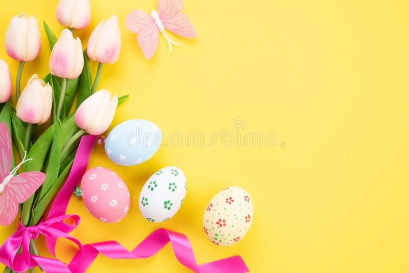 Happy easter! Colourful of Easter eggs in nest with pink tulip flower and Feather on yellow paper background royalty free stock image