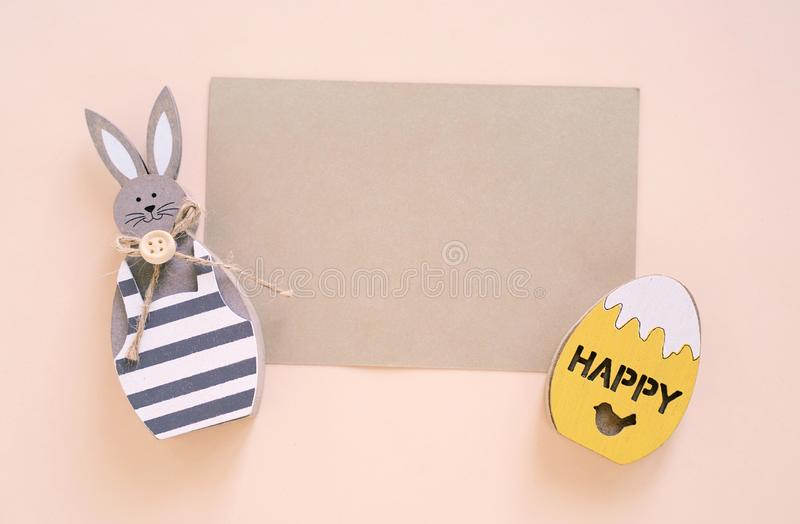 Happy Easter concept with blank card, wooden bunny and colorful easter eggs on yellow background stock photos