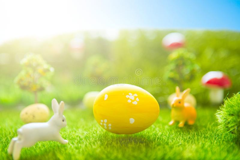 Happy Easter concept. Easter bunny and Easter eggs on green grass. Fairy tale sunset on the plastic green field with plastic grass stock image
