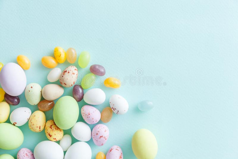 Happy Easter concept. Easter candy chocolate eggs and jellybean sweets  on trendy pastel blue background. Simple stock photography